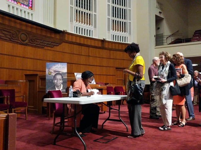 Author happily signs books following the discussion: Photo Credit: Telisa Hassen